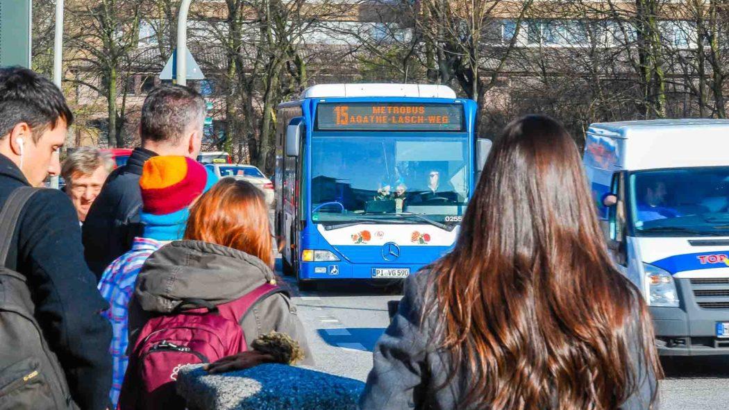 Menschen warten auf einen Metrobus der Linie M15 in Hamburg