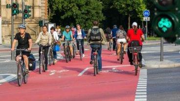 Radfahrer überqueren Straße auf Radspur an der Universität in Hamburg