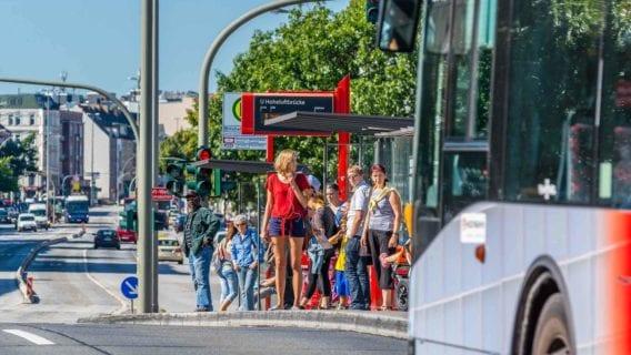 Menschen warten an der Hoheluftbrücke auf einen Bus der Linie M5.
