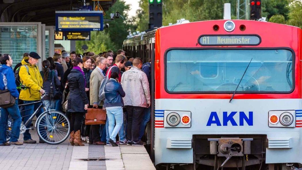 Menschen steigen in AKN-Triebwagen im S-Bahnhof Hamburg-Eidelstedt