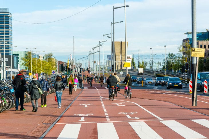 Radfahrer fahren auf breiter Fahrradspur in Amsterdam