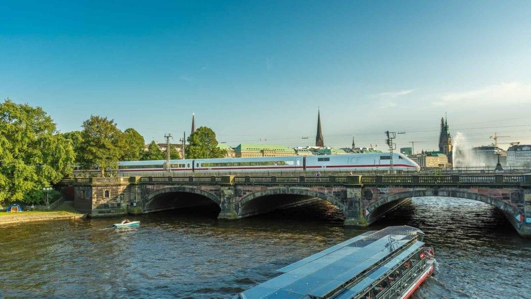 Ein ICE passiert die Lomardsbrücke in Hamburg bei tiefstehender Abendsonne im Sommer