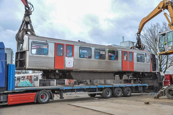 Zwei Bagger heben einen alten Hamburger U-Bahnwagen vom Tieflader