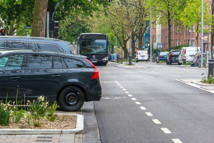 Schräg stehende Falschparker blockieren Teile des Fahrrad-Schutzstreifens. Zwischen Fahrzeugheck und Bus ist der Raum für Radfahrer lebensgefährlich eng