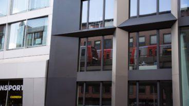 Zwei U-Bahnzüge vom Typ DT5 spiegeln sich in einem Bürogebäude in Hamburg