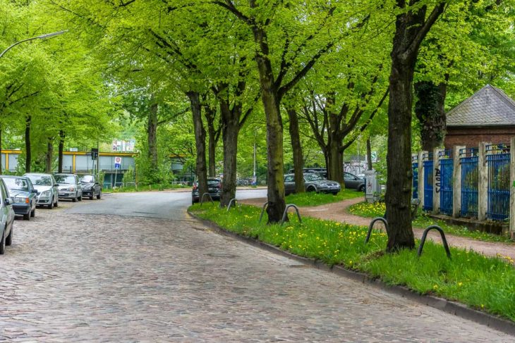 Diese beschauliche Kopfsteinpflasterstraße wird die zentrale Zuwegung zum neuen Fernbahnhof Altona sein. Hinter den Bäumen (beim S-Bahn-Logo) wird das neue Empfangsgebäude stehen. Rechts das Thyssen-Krupp-Gelände.