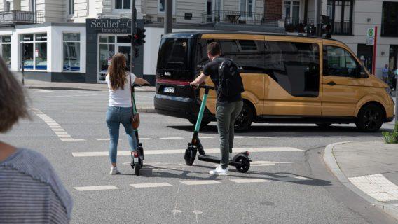 Neue Mobilität: Zwei E-Scooter-Fahrer stehen an einer Ampel in Hamburg-EImsbüttel. Im Hintergrund ein Bus des Ridesharing-Anbieters Moia