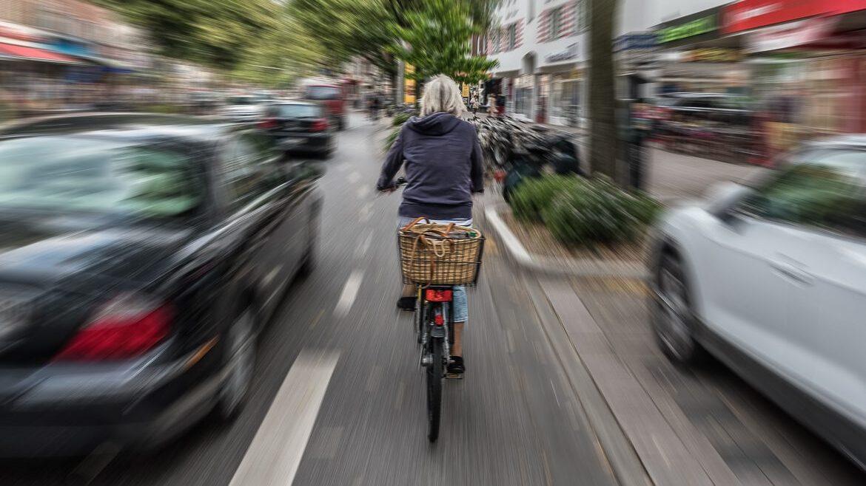 Ein PKW überholt eine Radfahrerin in der Osterstraße in Hamburg mit sehr geringem Abstand.
