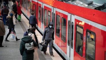 Ein Fahrgast mit einer Mundschutz-Maske vor einer S-Bahn in Hamburg