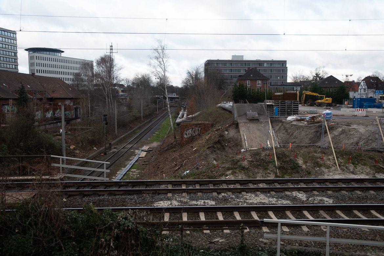 Hasselbrook: Im Vordergrund liegen die Gleise der Strecke Hamburg - Lübeck, unten kreuzt die Güterumgehungsbahn. Die Gleise der S4 sollen hinter den beiden Fernbahngleisen die Güterumgehungsbahn überqueren. Derzeit laufen die ersten Arbeiten für eine provisorische Brücke über die Güterumgehungsbahn. Darüber sollen Baumaschinen eine Kleingartensiedlung am linken BIldrand erreichen, die derzeit von mehreren Bahnstrecke voll umschlossen ist und von Straßenfahrzeugen nicht erreicht werden kann.