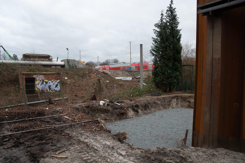 Das Baumaterial und die Maschinen für die Spundwand wurden offenbar auf Arbeitswaggons per Schiene direkt bis an die Baugrube herangefahren. Ungefähr ím Bereich des Betonpfeilers in der Bildmitte werden die S4-Gleise später die Güterumgehungsbahn überqueren - parallel zur Bahnstrecke Hamburg - Lübeck im Bildhintergrund.