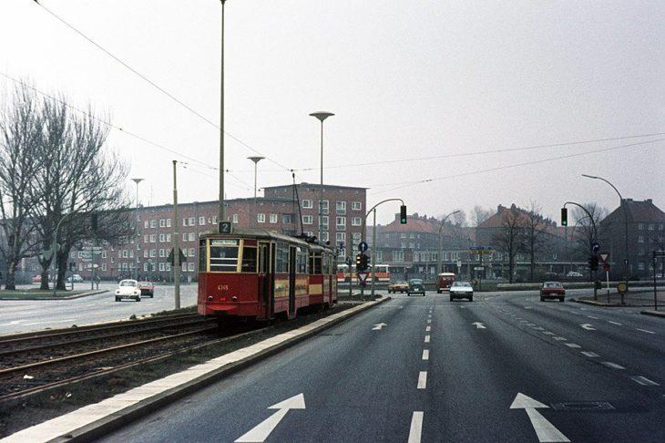 """Eine Hamburger Straßenbahn der Linie 2 fährt in der Sievekingsallee auf die Haltestelle """"Horner Rennbahn"""" zu. Die Gleise sind modern und unabhängig vom Autoverkehr trassiert."""